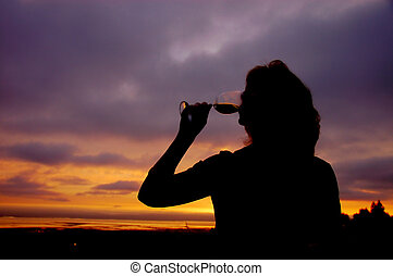 Beautiful middle aged woman drinking a glass of wine on her deck at sunset