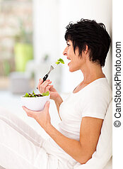 beautiful middle aged woman eating salad