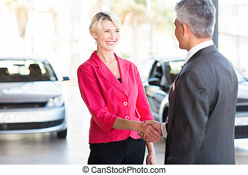 middle aged woman handshaking with car dealer