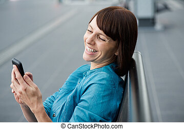 Beautiful middle aged woman looking at cell phone