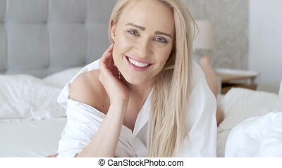 Beautiful middle aged woman lying on the bed, wearing white...