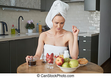 Beautiful middle aged woman sitting in her kitchen in the morning