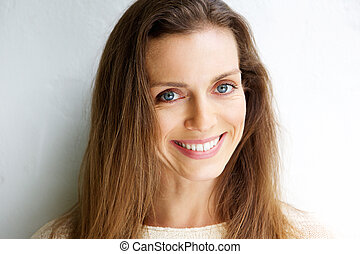 Beautiful middle aged woman smiling against white background