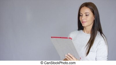 Beautiful middle aged woman using tablet computer while...