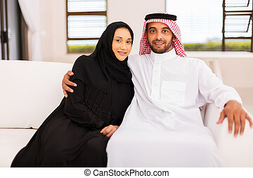 middle eastern couple relaxing on the couch