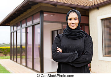 middle eastern woman standing in front of her house