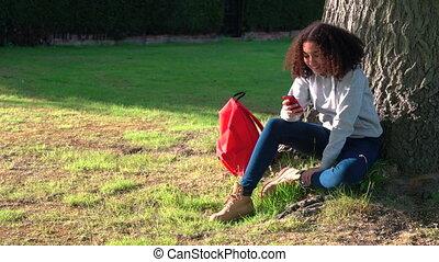 Beautiful mixed race African American girl teenager using a...