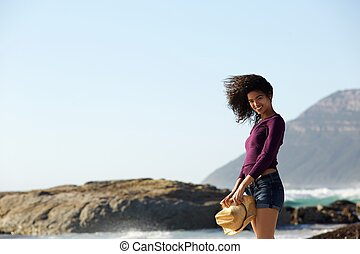 Beautiful mixed race girl smiling at the beach