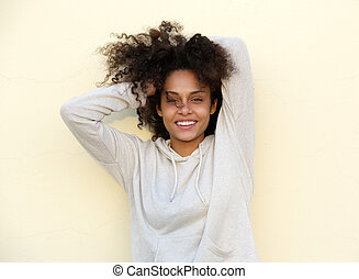 Beautiful mixed race woman smiling with hand in hair