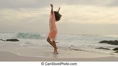 Beautiful mixed-race woman spinning on the beach