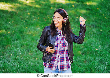 Beautiful mixed race young woman listening to music on headphones with smartphone. Hispanic hipster girl dancing to rhythm and singing along melody in the park.