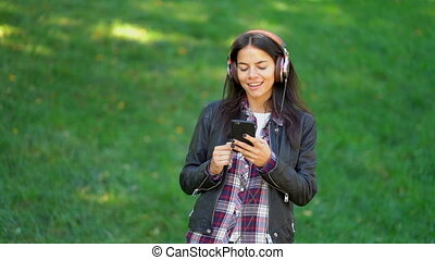 Beautiful mixed race young woman listening to music on...