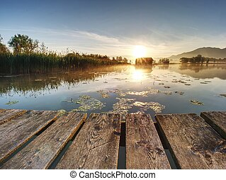 Beautiful mmorning at lake with traditional wooden boat house.