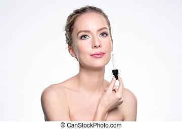 Beautiful model applying a cosmetic skin serum treatment on white