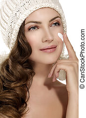 beautiful model applying a creme on face protection from winter