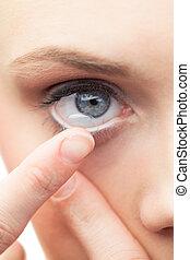 Beautiful model applying contact lens