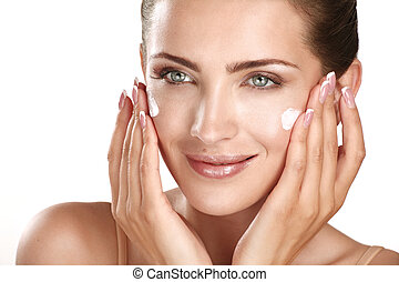 beautiful model applying cosmetic cream treatmen on her face on white