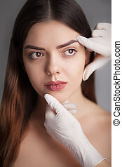 beautiful model applying cosmetic cream treatment on her face