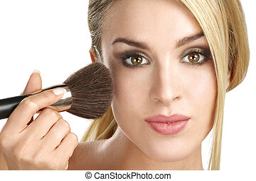 beautiful model applying professional make up using a brush