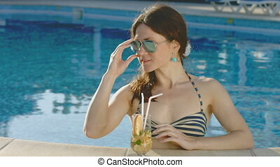 Beautiful model drinking cocktail in pool, looking at camera