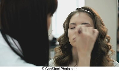 Beautiful model gets a professional makeup done by the...