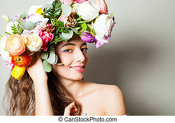 Beautiful model girl with a wreath of spring flowers. Cosmetics , beauty and cosmetology