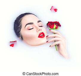 Beautiful model girl with bright makeup holding red rose flower in her hand and relaxing in milk bath