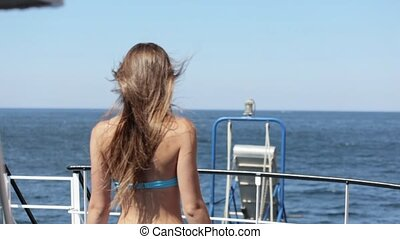 Beautiful model in a bikini standing with her back on the ship