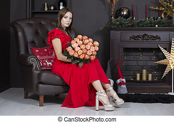 Beautiful model in an armchair. Luxury girl sitting on a leather chair with a bouquet of roses. Young woman in a red dress