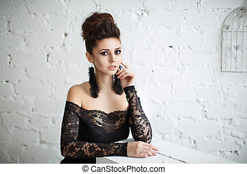 Beautiful model in black dress with evening makeup and hairdo posing