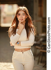Beautiful model in white stretch clothes on urban brick wall background closeup