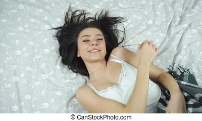 beautiful model lying on the bed in the hotel and posing for photos