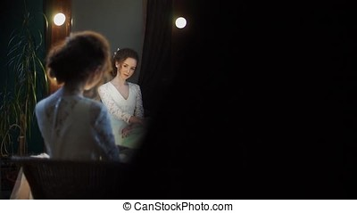 beautiful model of the bride sits in front of the mirror and straightens the wedding dress with her hands.