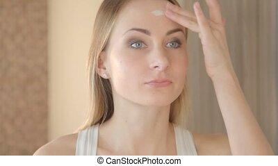 Beautiful model putting face cream in bathroom.