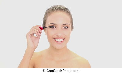Beautiful model putting mascara on on white background