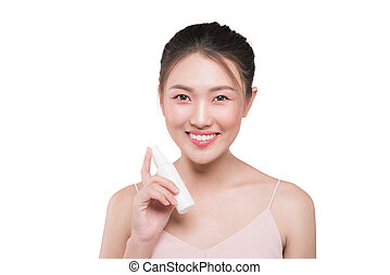 Beautiful model showing applying cosmetic cream treatment on her face