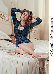 Beautiful model sitting on the bed