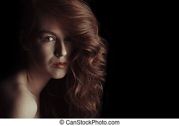 Beautiful model with curly hair in the shadows