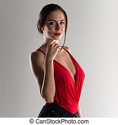 Beautiful model woman posing in studio with a sexy red dress