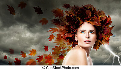 Beautiful Model Woman with Autumn Leaves. Storm Cloudy Sky, Blowing Leaves, Fashion Makeup and Perfect Beauty