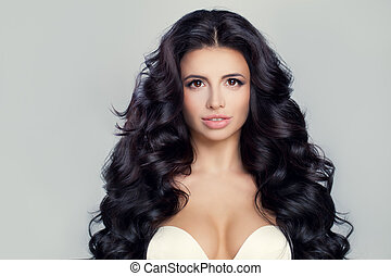 Beautiful Model Woman with Curly Hairstyle. Brunette Girl with Long Shiny Wavy Hair. Woman Face.
