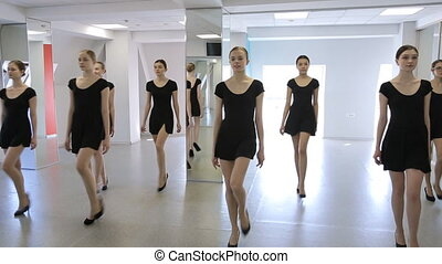 Beautiful models practice in catwalk on group lesson