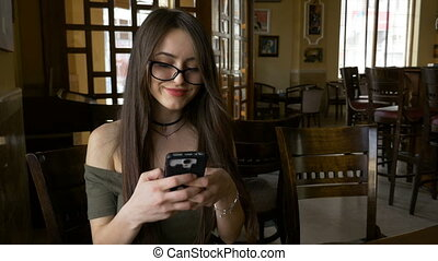 Beautiful modern young woman chatting on her smart phone and taking selfie to send her friend