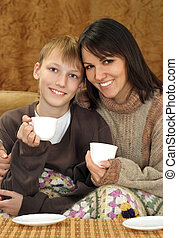 Beautiful mom and child sitting on the couch with a cup