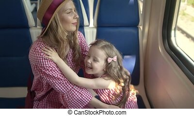 Beautiful mom and cute daughter playing patty-cake sitting in front of window in speed train