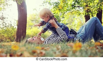 Beautiful mom and cute kid lying on the grass in autumn park, happy family in nature concept in slowmotion. 1920x1080