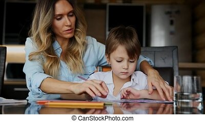 Beautiful mom helps her son to paint with colored pencils image. Helping to develop a child's imagination.