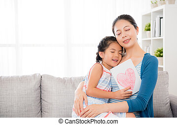 beautiful mom holding lovely little daughter hug