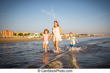 beautiful mom play with her children in the sea