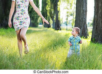 Beautiful mom playing in the park with her kid